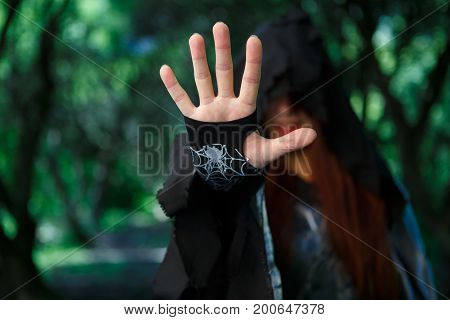 Image of witch in hood with outstretched hand in forest