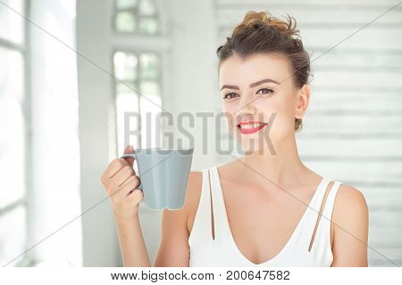 Cute young European woman enjoying a cup of coffee or tea while relaxing in Bright white room.