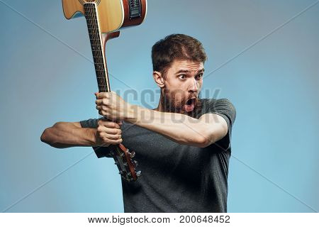 Man with a beard on a blue background swings a guitar, emotions, a musician.