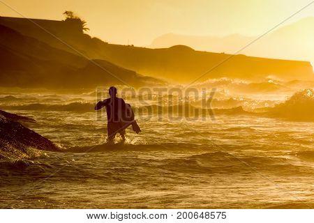 Bodyboarder walkimg in the water at Ipanema tropical sunrise in Rio de Janeiro