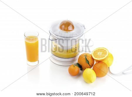 Electric citrus juicer, a glass of juice and fruit on a white background closeup