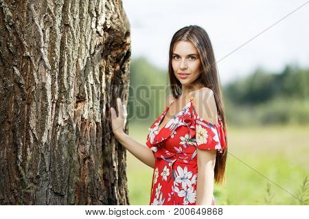 Outdoors portrait of beautiful brunette girl looking at camera