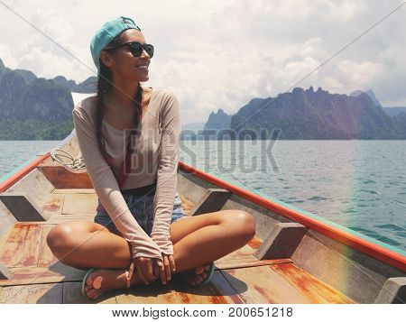 Young Happy Caucasian Mixed Race Girl Sitting and Relaxing on Traditional Thai Wooden Long Tail Boat at Khao Sok Lake. Phang Nga Province, Thailand.