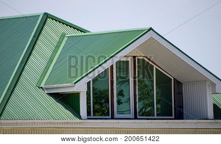 The House With Plastic Windows And A Green Roof Of Corrugated Sheet. Green Roof Of Corrugated Metal
