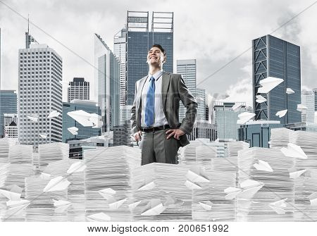 Confident businessman in suit standing on pile of documents among flying paper planes with cityscape on background. Mixed media.