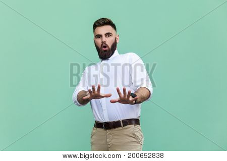 Not me! Stylish bearded man with shocked. Businessman having amazed face looking at camera. Indoor studio shot light green background