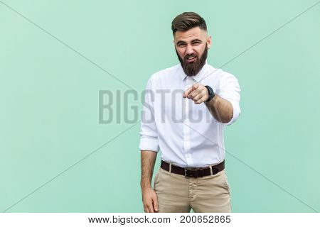 The bearded man pointing finger at camera and mockery over someone. Indoor studio shot