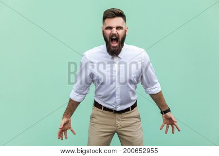Mans roar! The angry businessman screaming with closed eyes. Indoor studio shot. Light green background