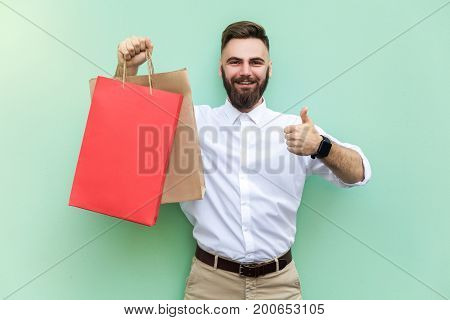 Online shopping or banking. Young adult businessman thumbs up and looking at camera and toothy smile. Indoor studio shot