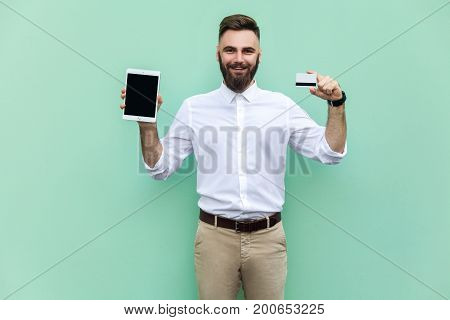 Online shopping or banking. Young adult businessman holding hands credit card and tablet and looking at camera and toothy smile. Indoor studio shot. Isolated on light green background
