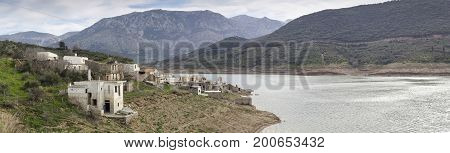 Deserted village on a lake surrounded by mountains (Crete, Greece)