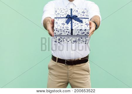 Its for you. Delivery man holding a box. Studio shot on light green background