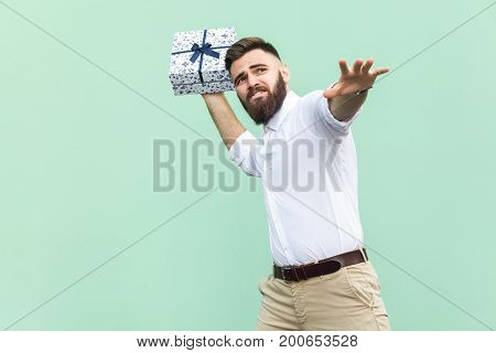 Catch your gift! Young adult man swung and wants to throw off your gift box isolated on light green background. Studio shot
