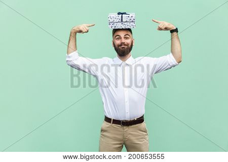 Your gift on my head. Funny young adult man holding gift box on head and pointing fingers on box. Light green background studio shot