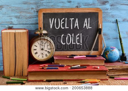 wooden-framed chalkboard with the text vuelta al cole, back to school in spanish written in it on a pile of old books, on a rustic wooden table full of pencil crayons and other retro school supplies