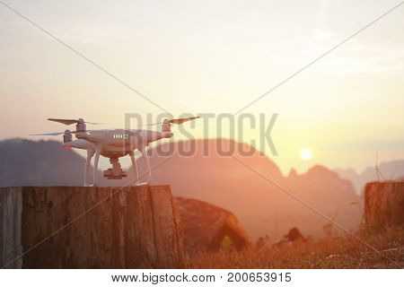 Quadcopter Drone Ready to Take Off. Modern Flying Gadget Waiting Command Against Beautifull Golden Sunset.