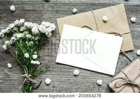 blank white greeting card with white flowers bouquet and envelope with gift box on rustic wooden background .top view. mock ups on rustic wooden background .top view. mock up