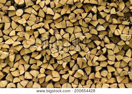 Wooden logs, beams, firewood, frame. A lot of wood. Wooden log wooden background. Fuel. Harvesting firewood for the winter. Logging