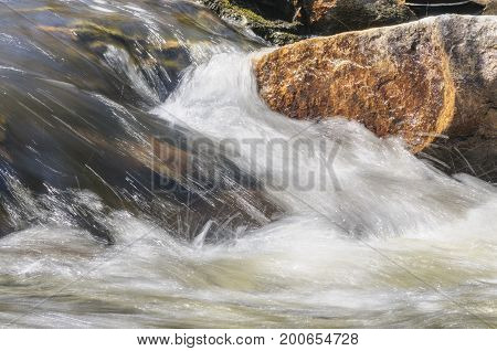 Water rushing over rocks at base of waterfall at Barden Reservoir