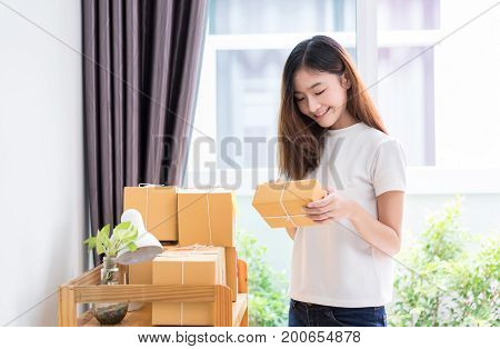 Young asian girl freelancer business private working at home office with sort box delivery online market on purchase orders to customer.