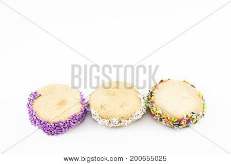 Three alfajores of cornstarch with grated coconut and colorful dragees. White background.