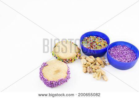 Ingredients for decorating cornstarch alfajores. On white background.