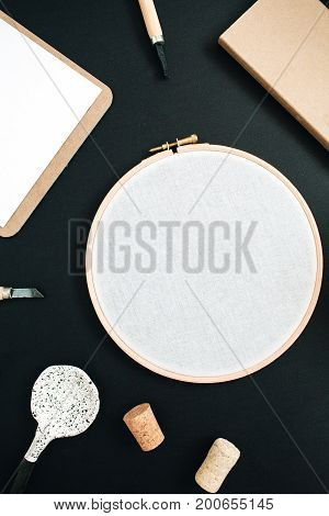 Embroidery frame clipboard handmade spoon on black chalk board background. Top view flat lay hipster workspace concept.