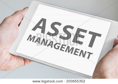 Asset management text displayed on touchscreen of modern tablet or smart device.