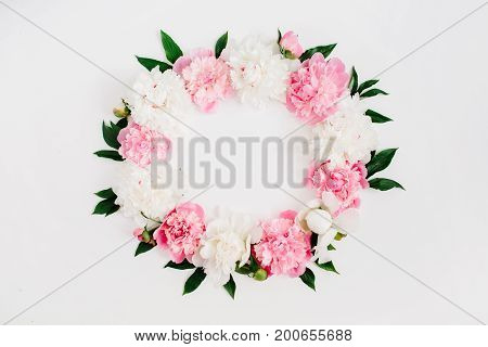 Frame wreath of pink peony flowers branches leaves and petals with space for text on white background. Flat lay top view. Peony flower texture.