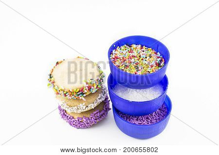 Row of three alfajores of cornstarch with dragees of different colors and grated coconut. Three tapers in line on dragees and grated coconut. White background.