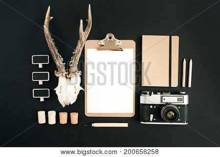 Top view flat lay hipster photographer concept. Retro camera goat horns clipboard craft diary on black chalk board background.
