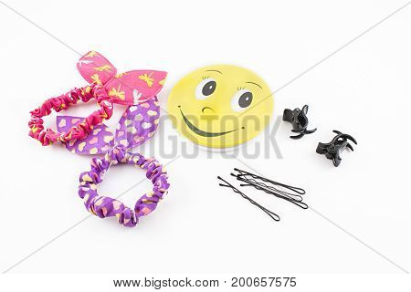Still life composed of hand mirror elastic bands clips and hair clips. White background.