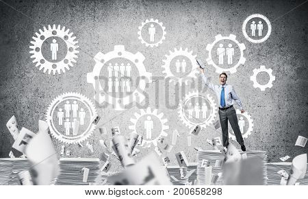 Businessman keeping hand with book up while standing among flying papers with social gear structure on background. Mixed media.