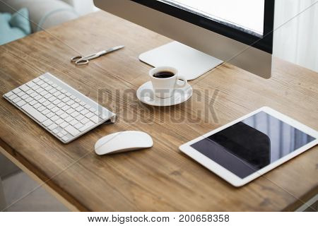 Picture of computer with accessories, scissors and camera on working desk