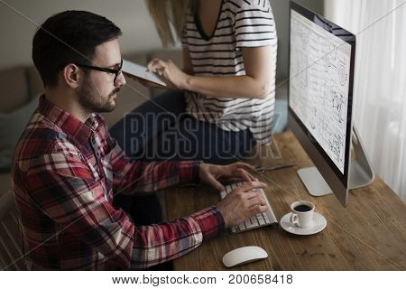 Beautiful woman and attractive man doing design work on computer