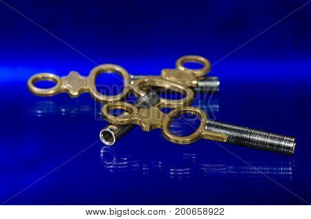 Three Antique Brass Pocket Watch Keys Laying on Blue Surface