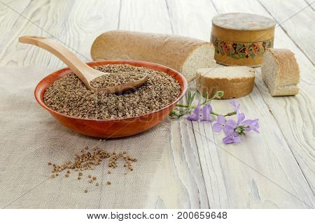 Bowl with dry buckwheat, spoon bread and buckwheat flour on a wooden table close-up