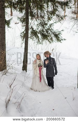 Bride and groom hugging in the park in winter. Beautiful man and woman in their wedding clothes are among the pines.