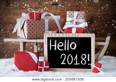 Sled With Christmas And Winter Decoration And Snowflakes. Gifts And Presents On Snow With Wooden Background. Chalkboard With English Text Hello 2018 For Happy New Year