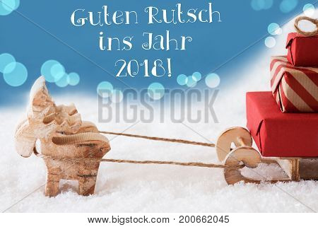 Moose Is Drawing A Sled With Red Gifts Or Presents In Snow. Christmas Card For Seasons Greetings. Light Blue Background With Bokeh Effect. German Text Guten Rutsch Ins Jahr 2018 Means Happy New Year