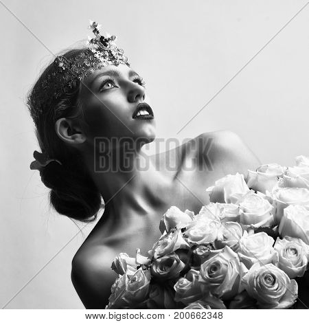 queen woman with luxury crown with diamond and gem has bare shoulders hold rose bouquet black and white