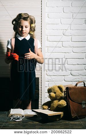 Small girl with curler in hair with typewriter. Education and childhood. Little baby secretary with bear and book. Kid choose career of journalist or writer. Child with briefcase and alarm clock. poster