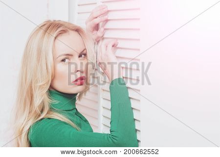 Woman With Long Blond Hair Posing At Window Shutters