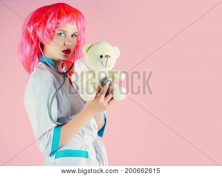 Girl examining teddy bear toy with stethoscope. Woman wearing medical uniform and red wig. Nurse on pink background. Doctor and patient. Health care and cure concept copy space