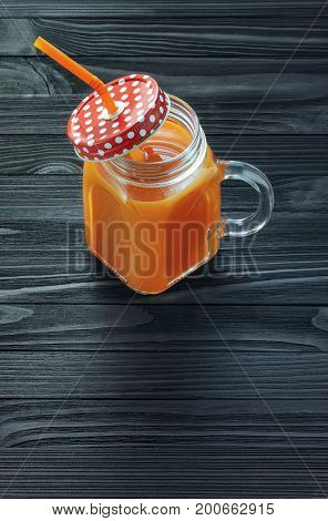 Fresh carrot juice in a glass jar with handle on a black wooden table. Carrot smoothie in a glass mug with a red lid in a white polka dots and an orange straw top view