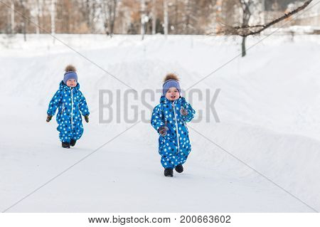 Twin boys walking in the Park in the winter in matching jumpsuits.