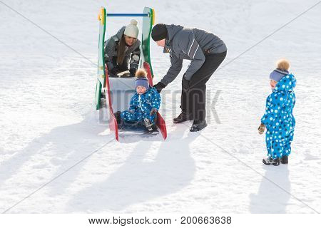 Twin brother rolls down hill, happy family winter walks in the Park.