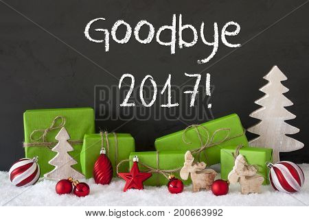English Text Goodbye 2017 For Happy New Year. Green Gifts Or Presents With Christmas Decoration Like Tree, Moose Or Red Christmas Tree Ball. Black Cement Wall As Background With Snow.