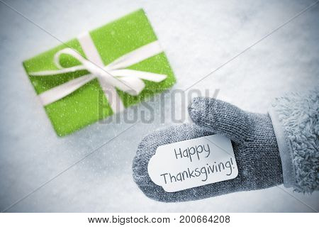 Glove With Label With English Text Happy Thanksgiving. Light Green Gift Or Present On Snow In Background. Seasonal Greeting Card With Snowflakes.