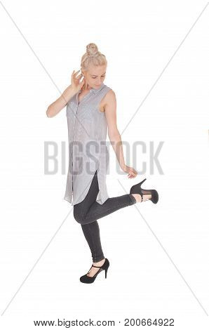 A lovely young woman standing in tights and a dress in profile with her blond hair in a knot isolated for white background